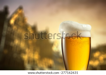 Glass of beer against blurred european city with beautiful lights on background at evening - stock photo