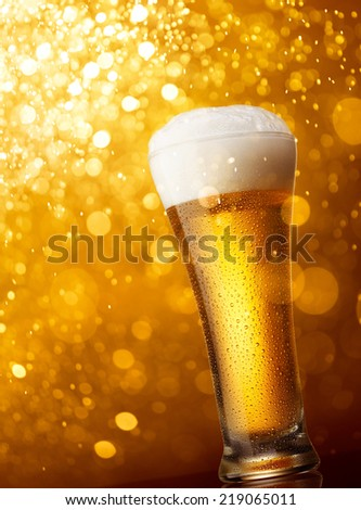 glass of beer against gold bokeh lights background - stock photo