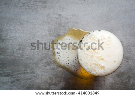 Glass of beer and a puddle of beer on a concrete table