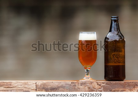 Glass of beer and bottle on wood table - stock photo