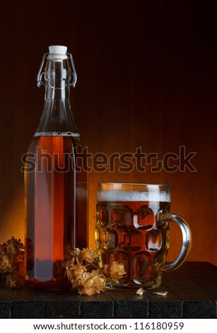 Glass of beer and bottle with hop on rustic wooden table still life