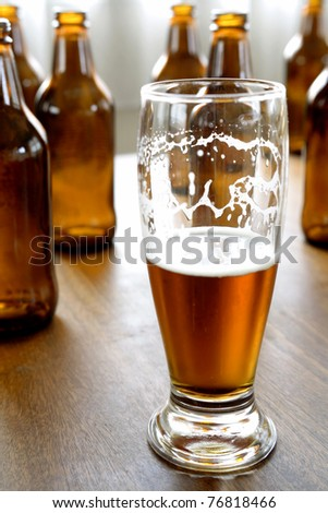 Glass of beer and bottles on table - stock photo