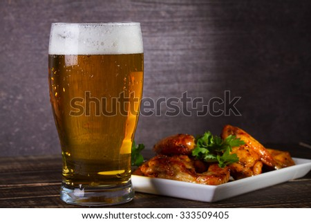 Glass of beer and chicken wings on dark wooden background - stock photo