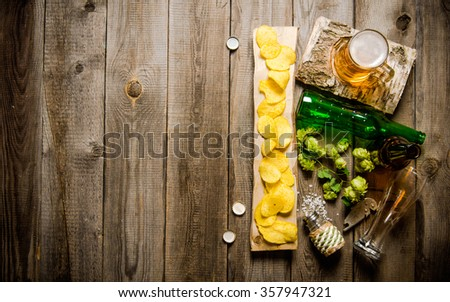 Glass of beer and chips on a wooden table. Top view - stock photo