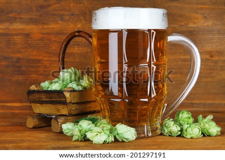 Glass of beer and hops, on wooden table - stock photo