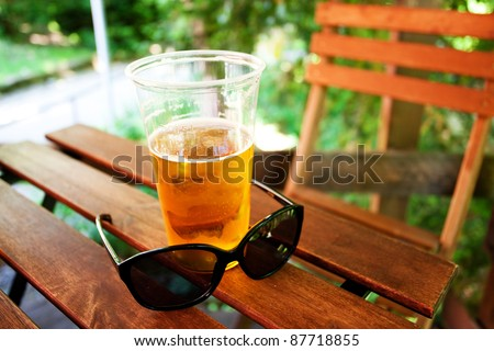 glass of beer and sunglasses standing on a wooden table - stock photo