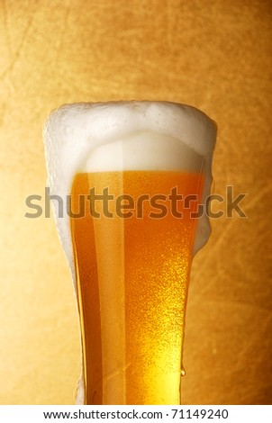 Glass of beer close-up over yellow background - stock photo