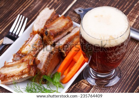 Glass of beer, grilled pork ribs and fresh carrot on wooden background - stock photo