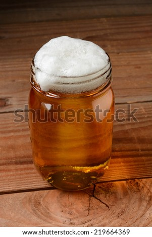 Glass of beer in a country bar setting served in a canning jar. Vertical format on a rustic wood background. - stock photo