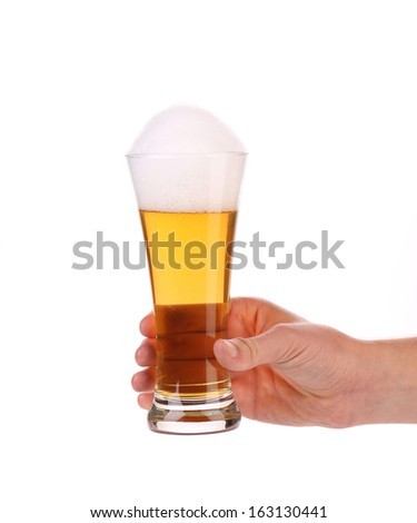 Glass of beer in hand. Isolated on a white background. - stock photo