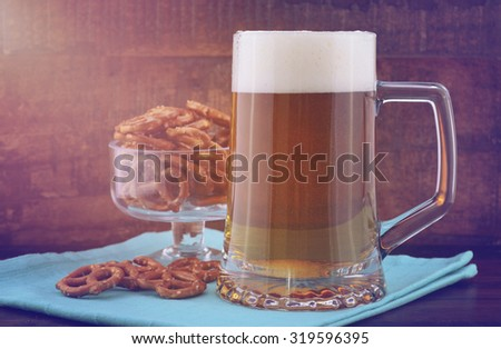Glass of beer in stein with mini pretzels on pale blue napkin on wood background with added retro vintage style filters and lens flare sun stream.  - stock photo