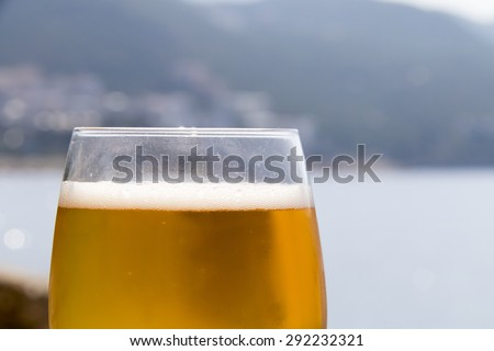 Glass of beer in the early morning on the beach