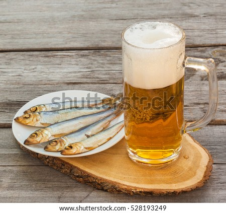 Glass of beer next to   plate  meats smoked fish  on a wooden table