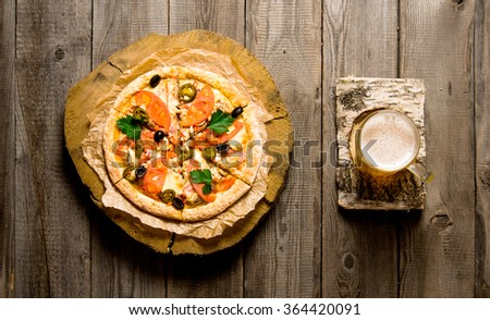 Glass of beer on a birch stand and the pizza on the wooden table. Top view - stock photo