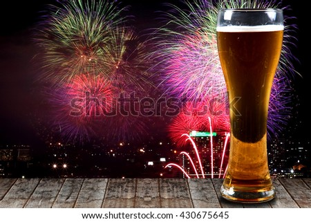 Glass of beer on a wooden background fireworks.Concept Festive Celebrations.