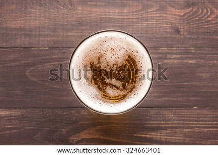 glass of beer on a wooden background. Top view. - stock photo