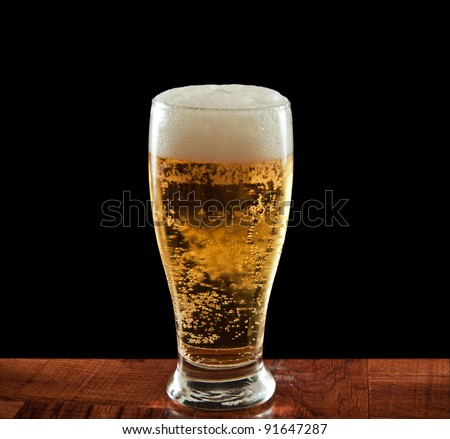 Glass of beer on a wooden bar isolated on a black background