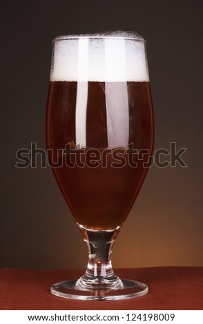 Glass of beer on brown background