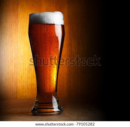 glass of beer on dark background with copy-space - stock photo