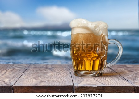 Glass of beer on empty wooden table with blurred sea on background, natural background with bokeh - stock photo