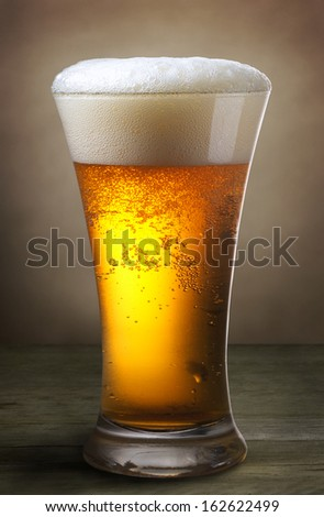 glass of beer on old wooden table - stock photo