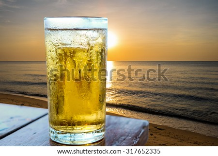 Glass of beer on the beach. - stock photo