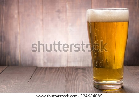 Glass of beer on the wooden backgorund. - stock photo