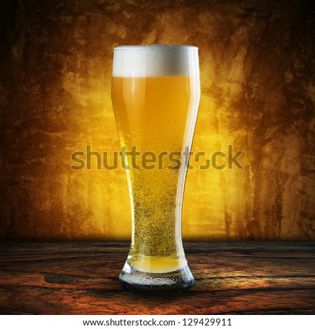 Glass of Beer on wood table with grunge wall - stock photo