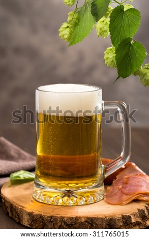 Glass of beer on wooden cut and hops branch with cones