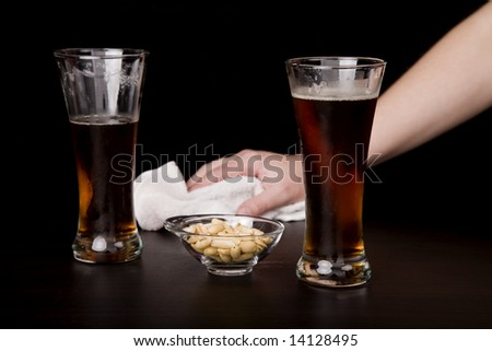 glass of beer with a waitress cleaning on the background - stock photo