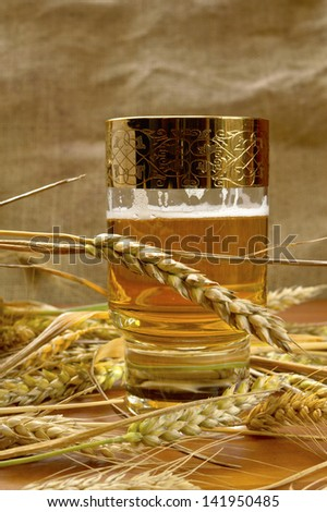 Glass of beer with barley on table. - stock photo