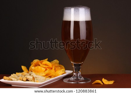 Glass of beer with crackers and chips on brown background - stock photo