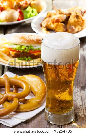 glass of beer with different snack - stock photo