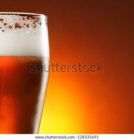 Glass of beer with froth close-up - stock photo