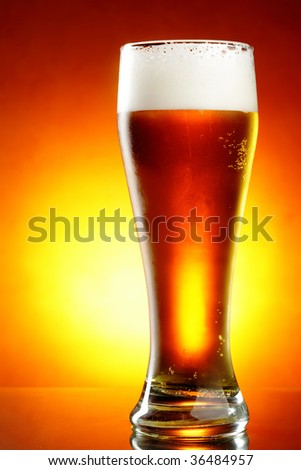 Glass of beer with froth close up - stock photo