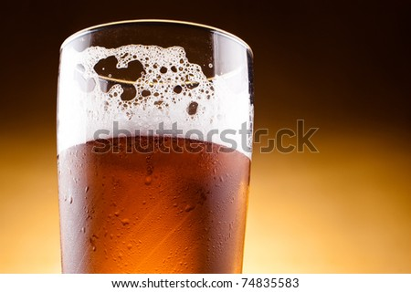 Glass of beer with froth close up on a yellow background - stock photo