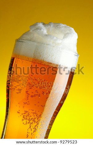 Glass of beer with froth close-up over yellow background