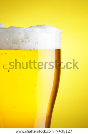 Glass of beer with froth close-up over yellow background - stock photo