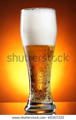 Glass of beer with froth over yellow background - stock photo
