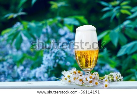 Glass of beer with garland of daisies, standing on the terrace in front of the garden - stock photo