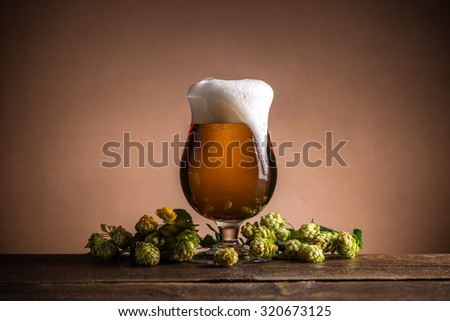 Glass of beer with hops on vintage wooden board - stock photo