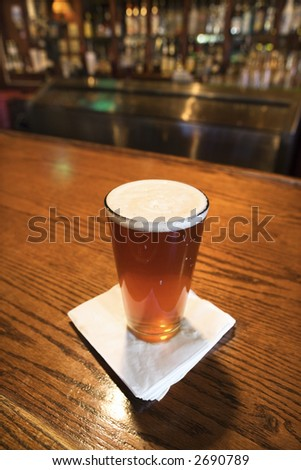 Glass of beer with napkin on bar. - stock photo