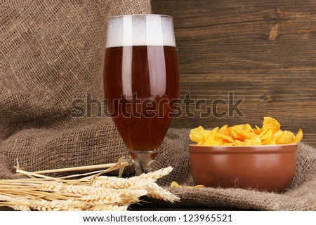 Glass of beer with plate of chips on wooden table on sacking background