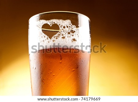 Glass of beer with the heart represented with froth close up over yellow background - stock photo