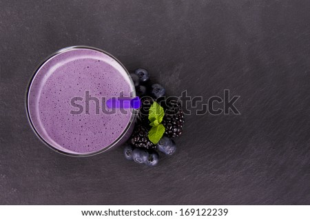 Glass of berry smoothie, isolated on slate plate. Top view. - stock photo