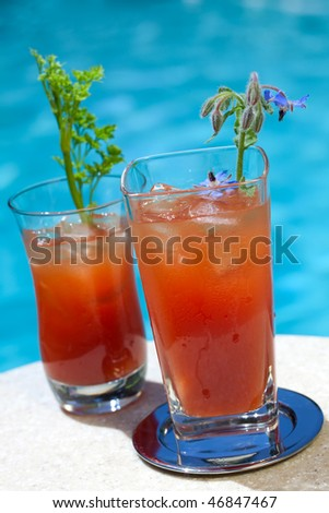 Glass of Bloody Mary alcohol cocktail garnished with borage flowers on swimming pool side outside of hotel in hot day, suited for vacation or travel theme - stock photo