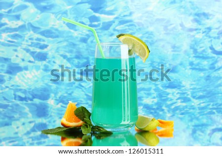 Glass of blue cocktail on blue background