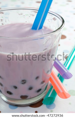 Glass of blueberry flavored pearl milk tea.