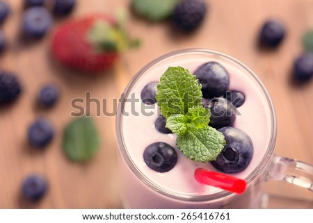 Glass of blueberry smoothie with mint on wooden table closeup top view - stock photo