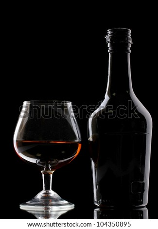 Glass of brandy and bottle on black background